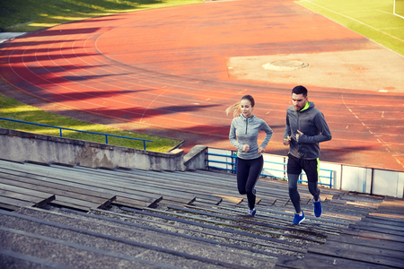 fitness, sport, exercising and lifestyle concept - happy couple running upstairs on stadium Stock Photo