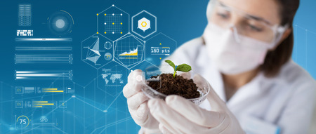 science, biology, ecology and research concept - close up of young female scientist wearing protective mask holding petri dish with plant and soil sample over blue background and virtual charts