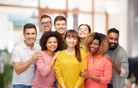 diversiteit, ras, etniciteit, vriendschap en mensen concept - internationale groep van gelukkige lachende mannen en vrouwen boven kantoor achtergrond