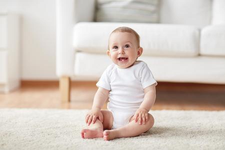 concept de l'enfance, la petite enfance et les gens - heureux petit bébé garçon ou une fille assis sur le sol à la maison