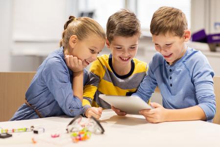 教育、科学、技術、子供、人々 の概念 - 幸せな子供またはタブレット pc コンピューター電気おもちゃをプログラミングとロボット学校レッスンでロ 写真素材