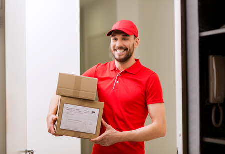 deliverer: delivery, mail, people and shipment concept - happy man in red uniform with parcel boxes in corridor at open customer door Stock Photo