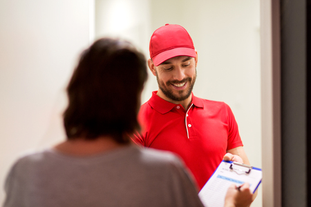 addressee: delivery, mail, people and shipping concept - happy man with clipboard and customer signing form at home