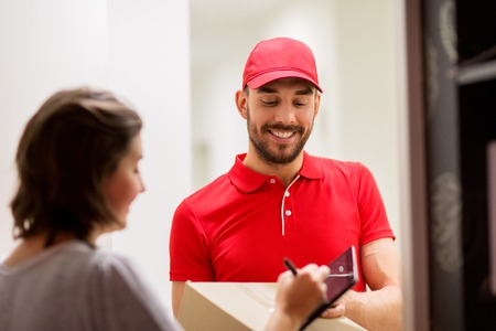 delivery, mail, people and shipping concept - happy man delivering parcel box and customer signing on tablet pc computer at home