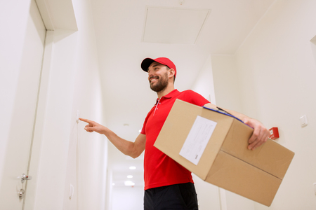 delivery, mail, people and shipment concept - happy man in red uniform with parcel box in corridor ringing doorbell Stock Photo