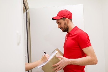 deliverer: delivery, mail, people and shipping concept - happy man with box and customer signing form at home