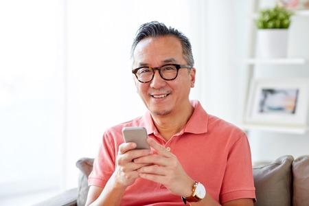 Technologie, personnes, style de vie et concept de communication - homme avec téléphone intelligent assis sur un canapé à la maison Banque d'images - 74947531