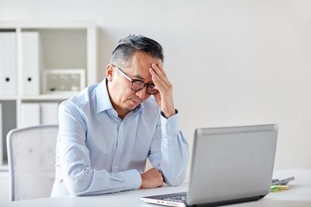 zaken, deadline, stress, mensen en technologie concept - zakenman in brillen met een laptop computer die lijden aan hoofdpijn op kantoor