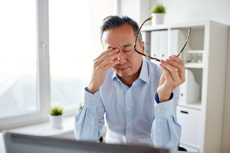 ビジネス、過労、期限、人コンセプト - 眼鏡とラップトップ コンピューターのオフィスで目をこすりながら疲れたビジネスマン