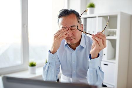 Negocio, exceso de trabajo, plazo y gente concepto - cansado hombre de negocios con gafas y computadora portátil computadora frotar ojos en oficina Foto de archivo - 74947551