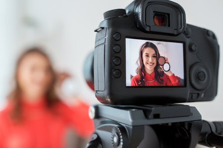 blogging, technology, videoblog, makeup and people concept - happy smiling woman or beauty blogger with bronzer and camera recording tutorial video at home Foto de archivo