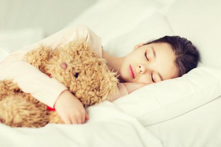 gente durmiendo: La gente, la niñez, el descanso y la comodidad concepto - niña durmiendo con juguetes de osito de peluche en la cama en su casa