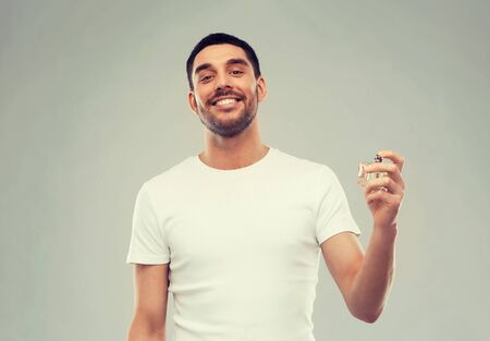perfumery, beauty and people concept - happy smiling young man with male perfume over gray background Stock Photo