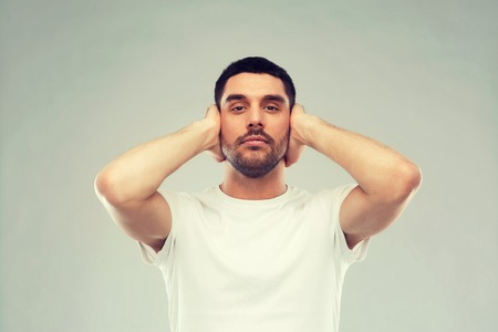 problem, emotion, stress, hearing problem and people concept - latin man covering his ears with hand palms