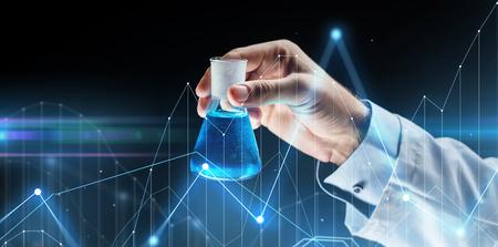 Wetenschap, chemie, onderzoek en mensenconcept - close-up van wetenschappelijke handholding testkolf met chemische en virtuele grafieken op donkere achtergrond