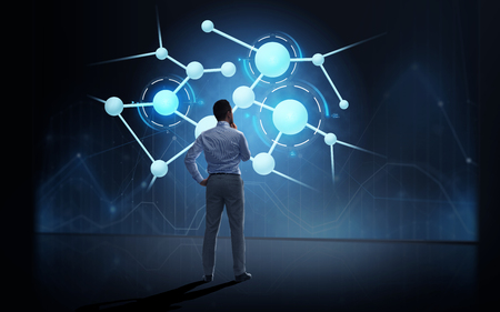 business, people, technology and science concept - businessman looking at virtual molecule projection over dark background from back