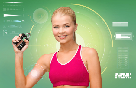 flexing: fitness, sport, training, exercising and people concept - smiling woman doing exercises with expander over green background Stock Photo