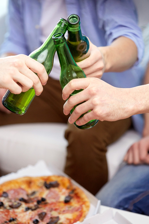 people, party, celebration and alcohol concept - close up of friends clinking beer bottles at home