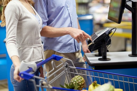 shopping, sale, payment, consumerism and people concept - couple with bank card buying food at grocery store or supermarket self-checkout Stock fotó