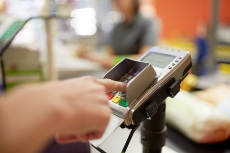 shopping, sale, consumerism and people concept - hand entering pin code at grocery store or supermarket cash register Stock Photo
