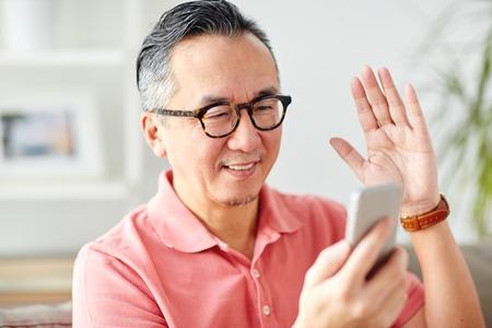 technologie, mensen, levensstijl en communicatie concept - gelukkige mens met smartphone die videovraag hebben thuis