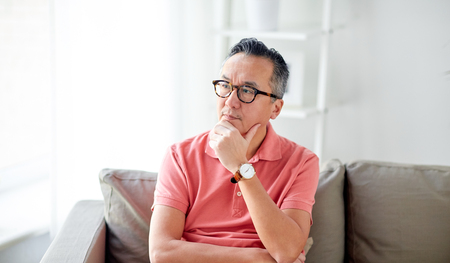 people concept - asian man thinking at home Imagens