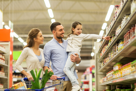 Familia con los alimentos en carrito de la compra en el supermercado Foto de archivo - 75150417