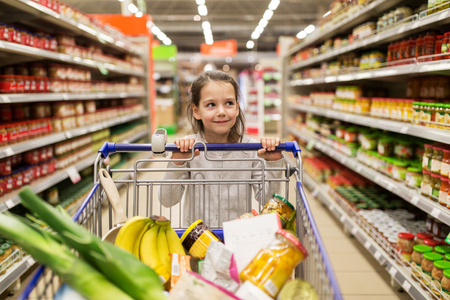 hypermarket: sale, consumerism and people concept - happy little girl with food in shopping cart at grocery store Stock Photo