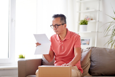 delivery, mail, consumerism and people concept - man with parcel box reading invoice at home