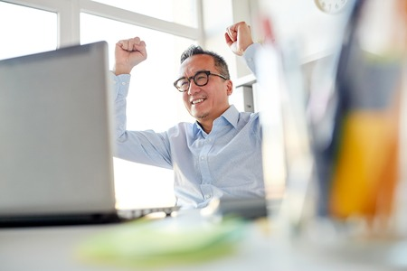business, people, success and technology concept - happy businessman with laptop celebrating victory at office