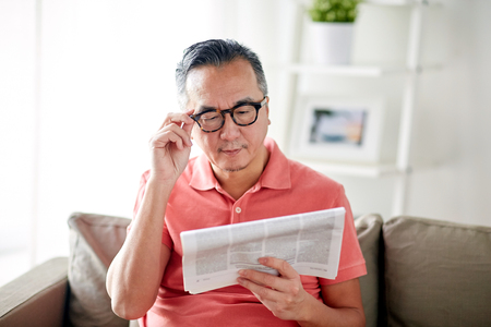 leisure, information, people and mass media concept - happy man in glasses reading newspaper at home