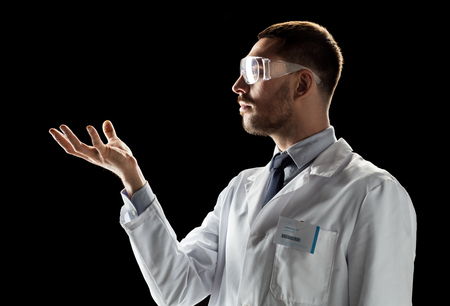 doctor or scientist in lab coat and safety glasses Stock Photo