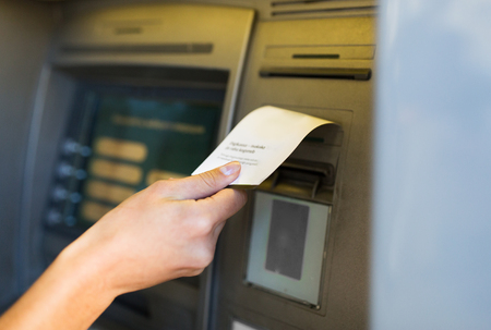 close up of hand taking receipt from atm machine