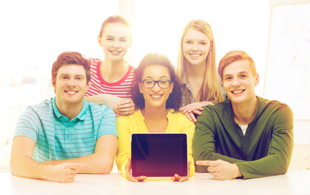 smiling students showing tablet pc blank screen photo