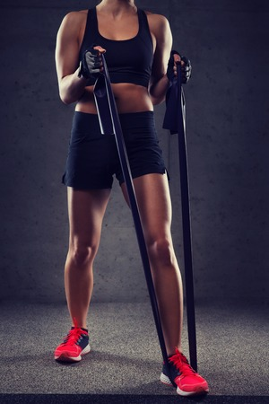 fitness, sport, training, people and lifestyle concept - close up of woman doing exercises with expander or resistance band in gym Imagens