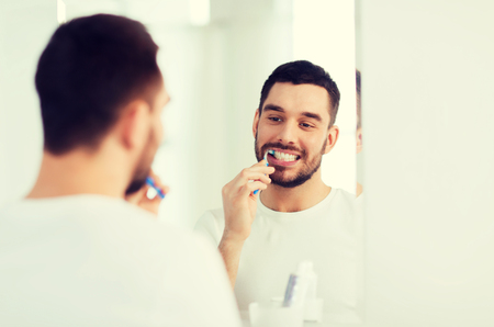 health care, dental hygiene, people and beauty concept - smiling young man with toothbrush cleaning teeth and looking to mirror at home bathroom 版權商用圖片