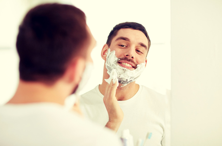 beauty, hygiene, shaving, grooming and people concept - smiling young man looking to mirror and applying shaving foam to face at home bathroom Stock Photo