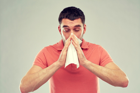 people, healthcare, rhinitis, cold and allergy concept - sick man with paper napkin blowing nose over gray background
