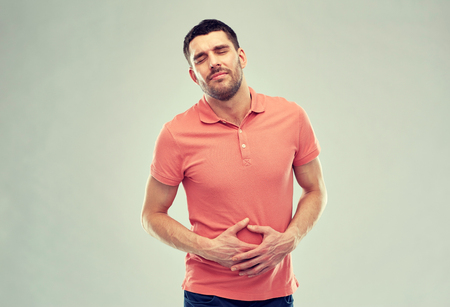 unhappy people: people, healthcare and problem concept - unhappy man suffering from stomach ache over gray background