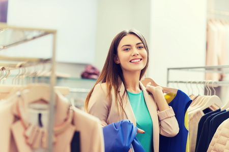 sale, shopping, fashion, style and people concept - happy young woman choosing clothes in mall or clothing store Stock Photo
