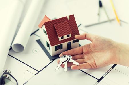 architettura, costruzione, costruzione, immobiliare e concetto di casa - mano con chiavi di casa e progetto
