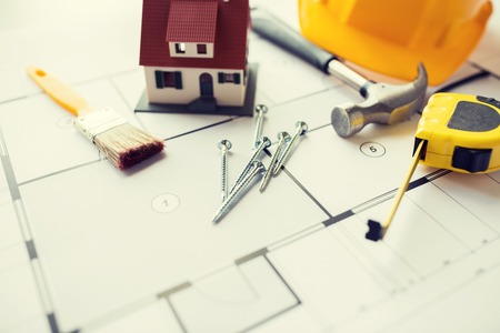 building estate: architecture, building, construction, real estate and home concept - close up of living house model on blueprint with repair tools Stock Photo