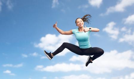 スポーツ、フィットネス、運動、人々 の概念 - 空気中のジャンプと青い空を背景に親指を現して幸せ笑顔の若い女性