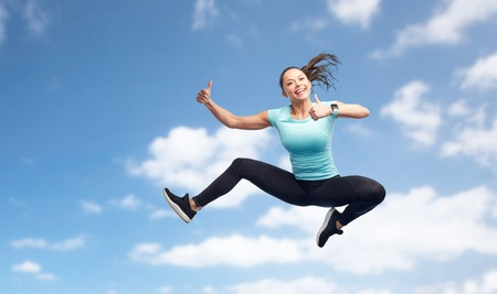 sport, fitness, motion and people concept - happy smiling young woman jumping in air and showing thumbs up over blue sky background