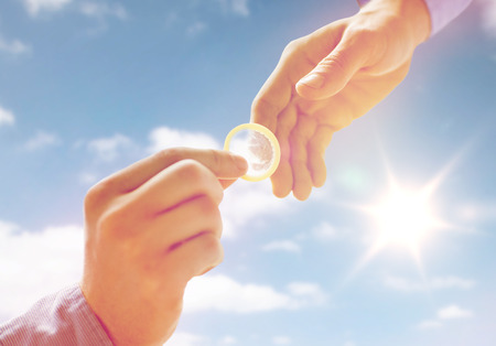 educacion sexual: people, homosexuality, safe sex, sexual education and charity concept - close up of happy male gay couple hands giving condom over sky and sun background