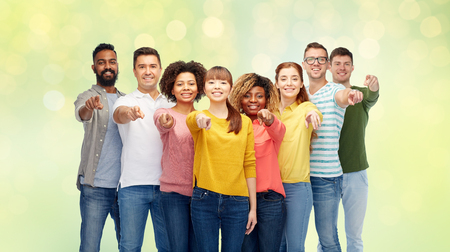 diversity, choice, ethnicity and people concept - international group of happy smiling men and women pointing finger on you over summer green lights background