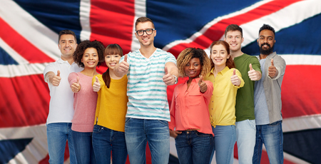 diversity, race, ethnicity, immigration and people concept - international group of happy smiling men and women showing thumbs up over english flag background