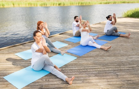 fitness, sport and healthy lifestyle concept - group of people making yoga exercise and meditating outdoors on river or lake berth Stock Photo