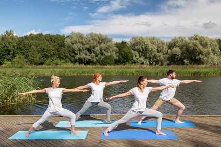 fitness, sport, and healthy lifestyle concept - group of people making yoga in warrior pose on river or lake berth Stock Photo