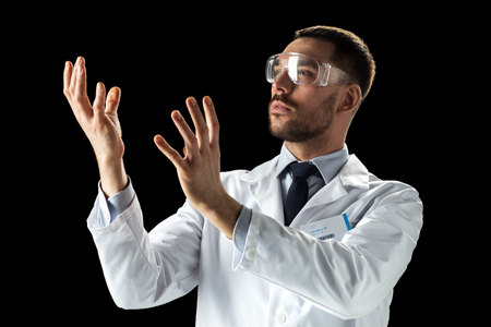 doctor or scientist in lab coat and safety glasses Imagens